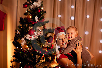 Mother with beautiful baby near Christmas tree