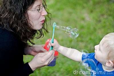 Mother blowing bubbles with toddler