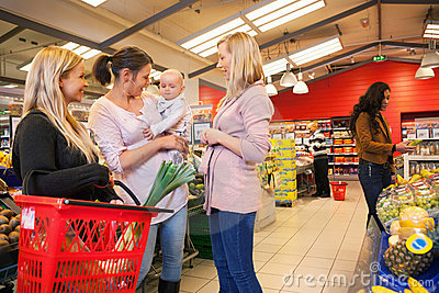 Mother carrying child with friends shopping