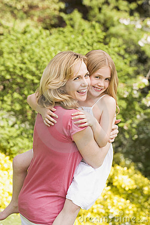 Mother carrying daughter outdoors smiling