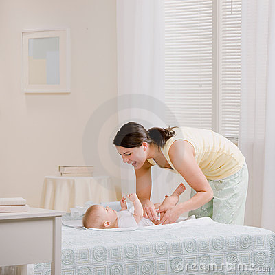 Free Mother Changing Baby�s Diaper On Bed Stock Image - 6568591