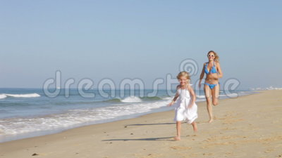 Mother Chasing Daughter Along Beach stock video