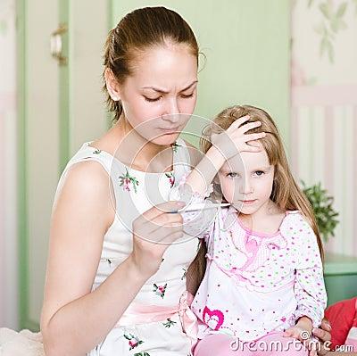 Mother checks temperature at  child