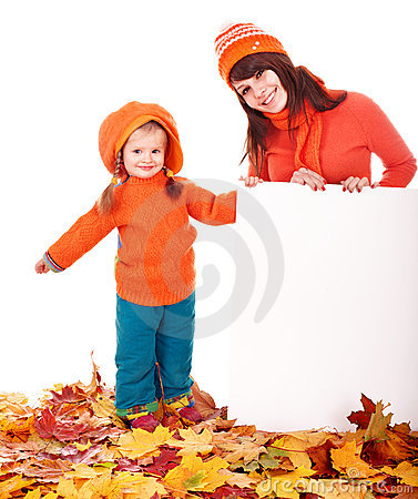 Mother with child on autumn leaves holding banner.