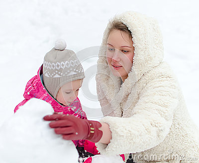 Mother and child making snowman