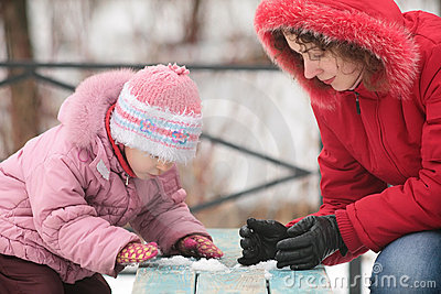 Mother with child play with snow on bench