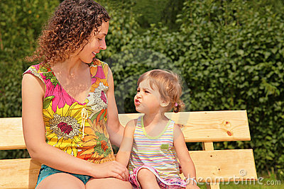 Mother and child sit on bench