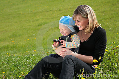 Mother with child sit on grass