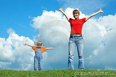 Mother and child stand on green grass