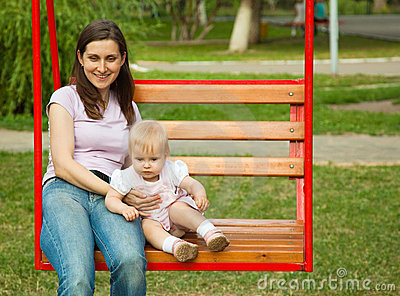 Mother and a child swinging in a playground