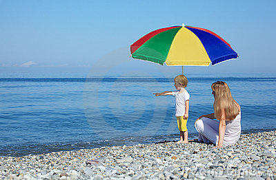 Mother with child under umbrella on pebble beach