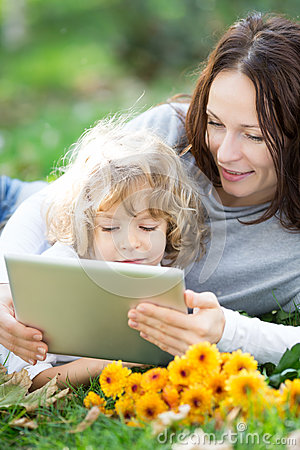 Mother and child using tablet PC outdoors