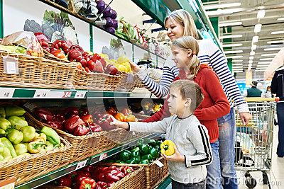 Mother and children with bell pepper in supermarket Stock Photo