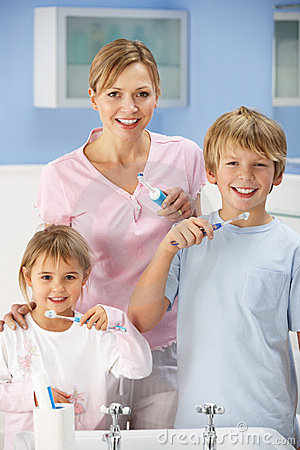 Mother and children cleaning teeth in bathroom