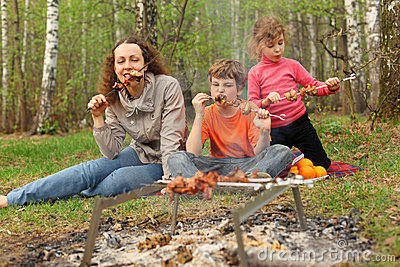 Mother and children eat grilled shish kebab