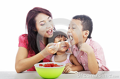 Mother and children eating fruit salad