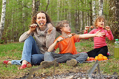 Mother and children finish to eat shish kebab