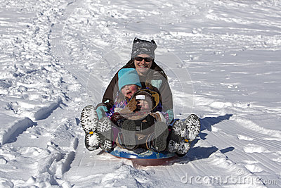 Mother and children have fun sliding down the sled hill