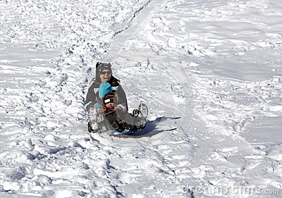 Mother and children having fun on the sled hill