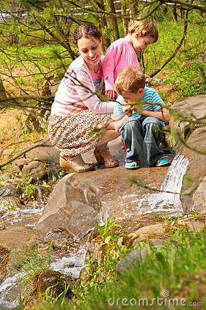Mother with children look on little waterfall