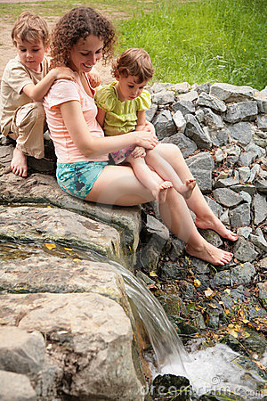 Mother with children look at small waterfall