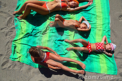 Mother and children lying on coverlet on beach