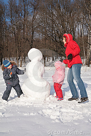 Mother and children make snowman