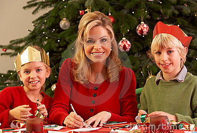 Mother And Children Making Christmas Cards Togethe