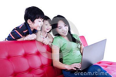 Mother and children relaxing on red sofa - isolated