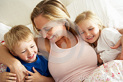 Mother And Children Relaxing Together In Bed