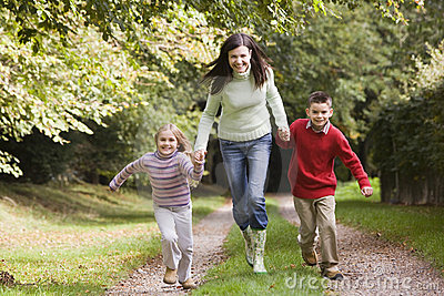 Mother and children running along woodland path