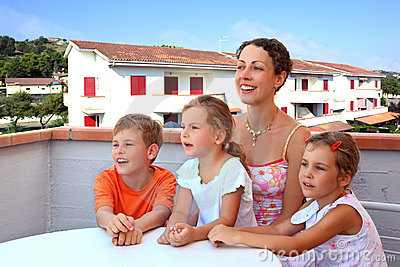 Mother and children sit in day-time on balcony