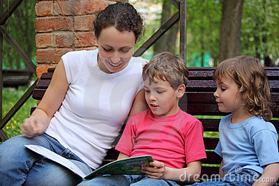 Mother with children sit and read book