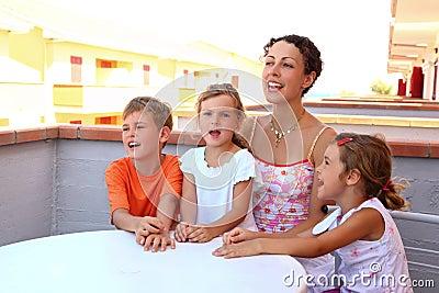 Mother and children sit on verandah in summer