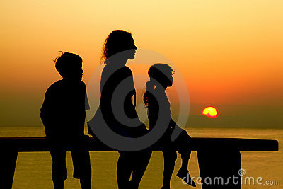 Mother with children sits on bench at beach