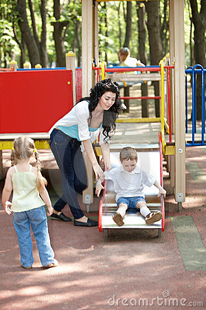 Mother with children on slide outdoor.