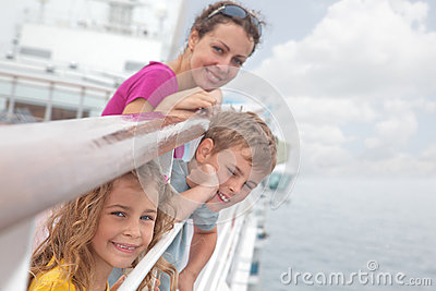 Mother with children stand on deck of ship