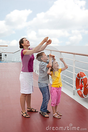 Mother with childrens launch kite from deck