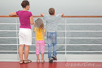 Mother with childrens stand on deck of ship