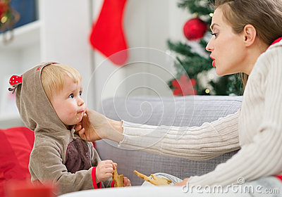 Mother cleaning eat smeared baby eating cookies