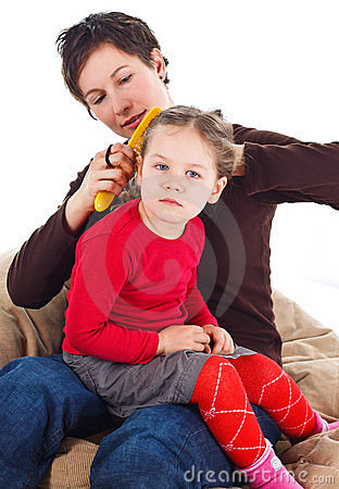 Mother combing daughter s hair