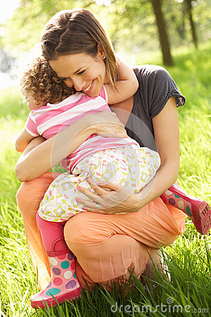 Mother Cuddling Young Daughter In Summer Field
