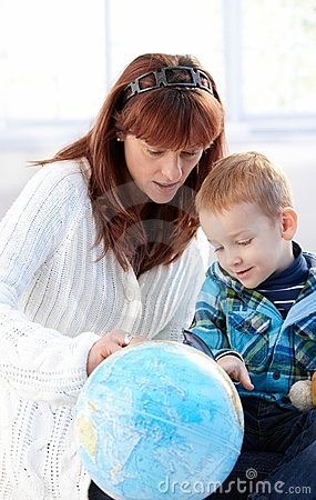 Mother and cute kid studying globe together