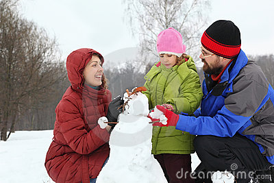 Mother and dad with daughter sculpt snowman Stock Photo