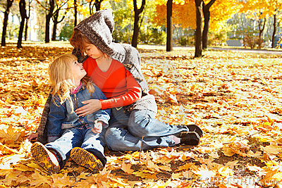 Mother and daughter in autumn leaves