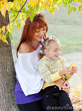 Mother and daughter are in autumn park