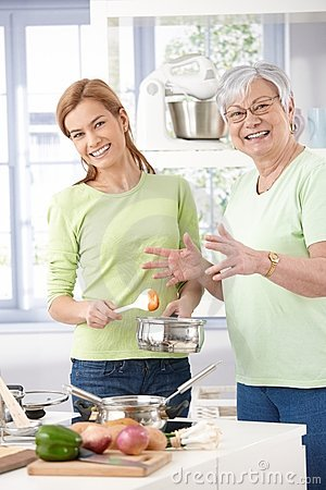 Mother and daughter cooking together smiling