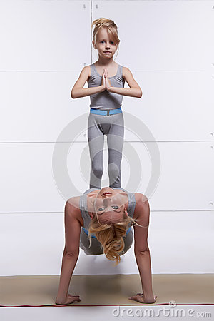 Mother and daughter doing yoga exercise, fitness, gym wearing the same comfortable tracksuits family sports paired woman p