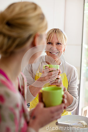 Mother and daughter drinking coffee in kitchen