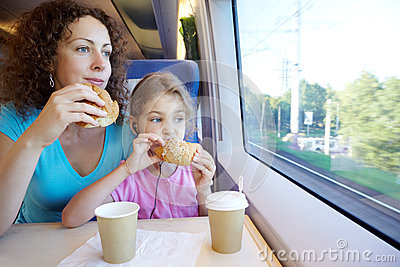 Mother and daughter eat near window of train